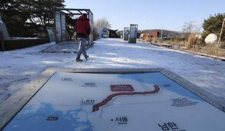 A visitor walks by a map of two Koreas at the Imjingak Pavilion in Paju, South Korea, Monday, Dec. 11, 2017. South Korea added several North Korean groups and individuals to its sanctions list Monday in a largely symbolic move that is part of efforts to cut off funding for the North's weapons programs. (AP Photo/Lee Jin-man)
