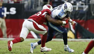 Arizona Cardinals inside linebacker Haason Reddick, left, brings down Tennessee Titans quarterback Marcus Mariota (8) during the second half of an NFL football game Sunday, Dec. 10, 2017, in Glendale, Ariz. The Cardinals defeated the Titans 12-7. (AP Photo/Ralph Freso)