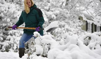 FILE - In this Saturday, Dec. 9, 2017 file photo, Laura Washington shovels her walk after a heavy snow, in Kennesaw, Ga. Thousands remained without electricity across the Deep South on Monday, Dec. 11, days after the storm snapped power lines across the region. Metro Atlanta got several inches of snow Friday and Saturday, while some areas farther north saw up to a foot of snowfall. (AP Photo/Mike Stewart, File)