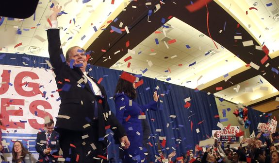 Confetti falls as Democrat Doug Jones and his wife Louise wave to supporters Tuesday, Dec. 12, 2017, in Birmingham, Ala. In a stunning victory aided by scandal, Democrat Doug Jones won Alabama's special Senate election on Tuesday, beating back history, an embattled Republican opponent and President Donald Trump, who urgently endorsed GOP rebel Roy Moore despite a litany of sexual misconduct allegations.  (AP Photo/John Bazemore)