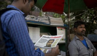 A Bangladeshi man reads a national newspaper that features news of 27-year-old Bangladeshi man Akayed Ullah, in Dhaka, Bangladesh, Tuesday, Dec. 12, 2017. Bangladesh counterterrorism officers are questioning the wife and other relatives of Ullah, who is accused of carrying out a bomb attack in New York City's subway system, officials said Tuesday. (AP Photo/A.M. Ahad)