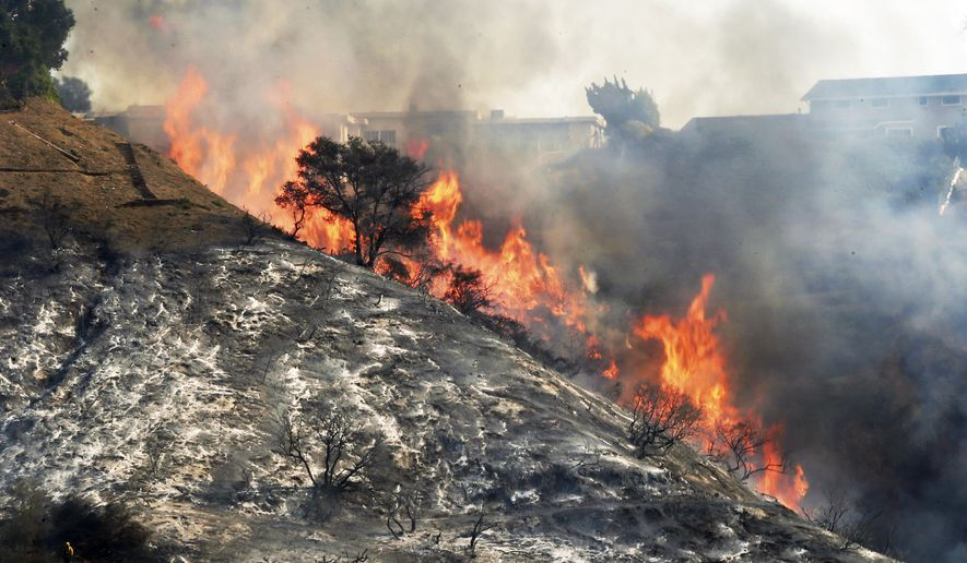 FILE - In this Wednesday, Dec. 6, 2017 file photo, flames sweep up a steep canyon wall, threatening homes on a ridge line as the Skirball wildfire swept through the Bel Air district of Los Angeles. The Los Angeles Fire Department said Tuesday, Dec. 12, 2017, that the wildfire that destroyed six homes and damaged a dozen more last week in the exclusive Bel Air section of Los Angeles was sparked by an illegal cooking fire in a homeless encampment. No one was in the camp, and no arrests have been made. (AP Photo/Reed Saxon, File)