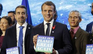 "French President Emmanuel Macron, center, attends the ""Tech for Planet"" event at the ""Station F"" start up campus ahead of the One Planet Summit in Paris, France, Monday Dec. 11, 2017. It is a dream come true for U.S.-based climate scientists  the offer of all-expenses-paid life in France to advance their research in Europe instead of in the United States under climate skeptic President Donald Trump, two of the winners say. (Philippe Wojazer, Pool via AP)"