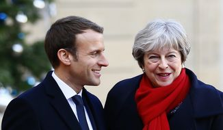 British Prime Minister Theresa May is welcomed by French President before a lunch at the Elysee Palace in Paris, Tuesday, Dec. 12, 2017. More than 50 world leaders are gathering in Paris for a summit that Macron hopes will give new momentum to the fight against global warming, despite U.S. President Donald Trump's rejection of the Paris climate accord. (AP Photo/Francois Mori)