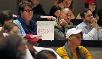 A protester holds a sign at a University of Oklahoma Board of Regents meeting in Oklahoma City, Tuesday, Dec. 12, 2017. About 100 protesters showed up at a regents meeting Tuesday seeking Regent Kirk Humphreys' resignation, after comments Humphreys made comparing gay people to pedophiles, but Humphreys, who was out of town, did not attend. The meeting ended with no discussion about the comments. (AP Photo/Sue Ogrocki)