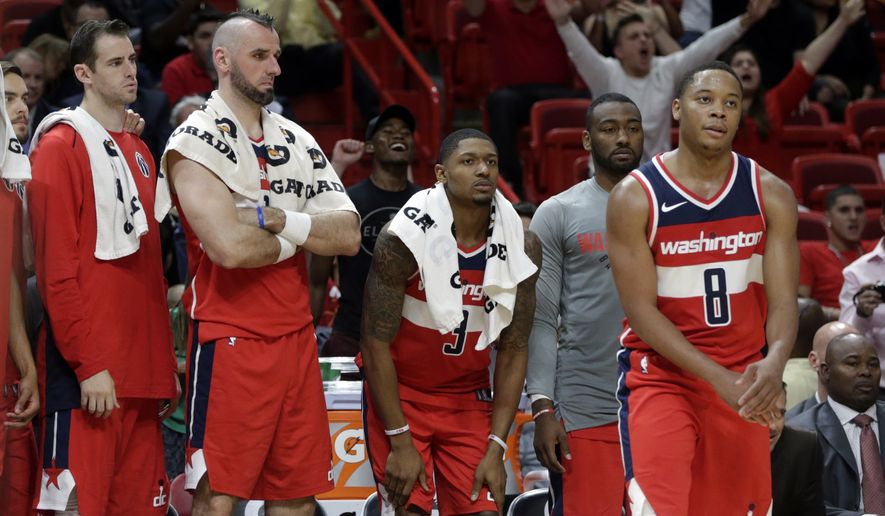 Washington Wizards' Jason Smith, left, Marcin Gortat, Bradley Beal, and Tim Frazier (8) watch during the second half of a preseason NBA basketball game against the Miami Heat, Wednesday, Oct. 11, 2017, in Miami. The Heat won 117-115. (AP Photo/Lynne Sladky)