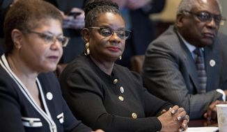 FILE- In this March 22, 2017, file photo, from left, Rep. Karen Bass, D-Calif., Rep. Gwen Moore, D-Wis., House Assistant Minority Leader James Clyburn of S.C., and other members of the Congressional Black Caucus meet with President Donald Trump in the Cabinet Room of the White House in Washington. Moore said on Tuesday, Dec. 12, that two people posing as Associated Press reporters telephoned her office, then spewed racial slurs. (AP Photo/Andrew Harnik, File)