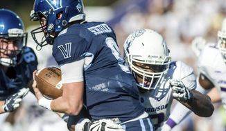 FILE - In this Oct. 14, 2017, file photo, James Madison defensive lineman Andrew Ankrah (93) latches onto Villanova quarterback Jack Schetelich (9) during the first half of an NCAA college football game in Harrisonburg, Va. Ankrah was selected for the The Associated Press FCS All-America first team on Tuesday, Dec. 12, 2017.  (Daniel Lin//Daily News-Record via AP, File)