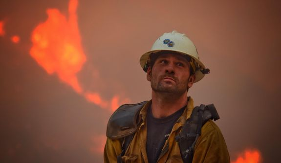 In this photo provided by the Santa Barbara County Fire Department, county fire hand crew member Nikolas Abele keeps an eye on a hillside for any stray embers during a firing operation in Santa Monica Canyon in Carpinteria, Calif., Monday, Dec. 11, 2017. Ash fell like snow and heavy smoke had residents gasping for air Monday as a wildfire exploded in size, becoming the fifth largest in state history. (Mike Eliason/Santa Barbara County Fire Department via AP)
