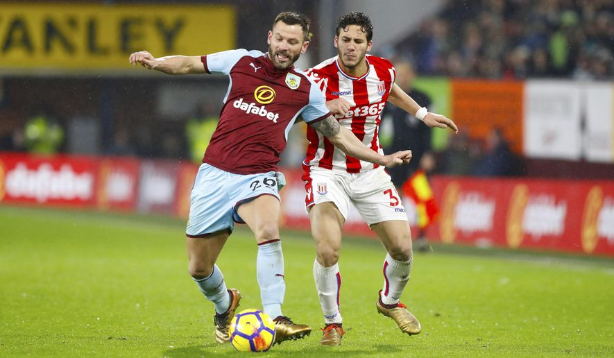 Burnley's Phil Bardsley, left, and Stoke City's Ramadan Sobhi vie for the ball during their English Premier League soccer match Burnley versus Stoke City at Turf Moor, Burnley, England, Tuesday, Dec. 12 2017. (Martin Rickett/PA via AP)