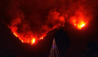 In this photo provided by the Santa Barbara County Fire Department, with flames burning behind it, a Christmas tree stands as a lone sentinel in the front yard of an evacuated home in Carpinteria, Calif., Monday, Dec. 11, 2017. Ash fell like snow and heavy smoke had residents gasping for air Monday as a wildfire exploded in size, becoming the fifth largest in state history. (Mike Eliason/Santa Barbara County Fire Department via AP)