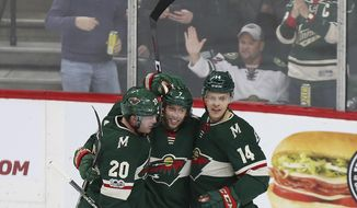 Minnesota Wild's Matt Cullen, center, celebrates with teammates Ryan Suter (20) and Joel Eriksson (14) after scoring a goal against the Calgary Flames in the first period of an NHL hockey game Tuesday, Dec. 12, 2017, in St. Paul, Minn. (AP Photo/Stacy Bengs)
