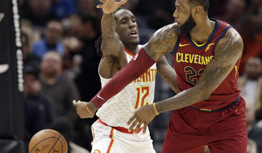 Cleveland Cavaliers' LeBron James, right, passes against Atlanta Hawks' Taurean Prince in the first half of an NBA basketball game, Tuesday, Dec. 12, 2017, in Cleveland. (AP Photo/Tony Dejak)