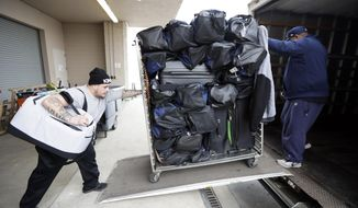 In this Dec. 8, 2017 photo, Troy Adams, left, and Levon Marlow of VIP Moving and Storage loads Tennessee Titans players' bags into a truck at the team's training facility in Nashville, Tenn., as the team prepares for a road trip to Phoenix and San Francisco. The franchise decided once the NFL schedule came out in mid-April to spend the week between back-to-back road games against the Cardinals and the San Francisco 49ers in Arizona. (AP Photo/Mark Humphrey)