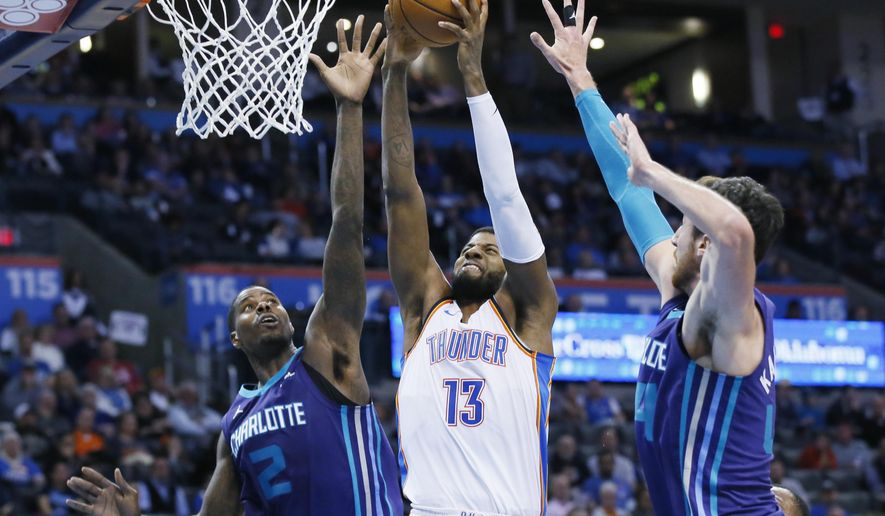 Oklahoma City Thunder forward Paul George (13) shoots between Charlotte Hornets forwards Marvin Williams (2) and Frank Kaminsky, right, in the fourth quarter of an NBA basketball game in Oklahoma City, Monday, Dec. 11, 2017. (AP Photo/Sue Ogrocki)