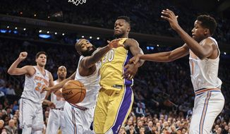 Los Angeles Lakers' Julius Randle, center right, competes for the ball with New York Knicks' Kyle O'Quinn, center left, during the first half of an NBA basketball game at Madison Square Garden in New York, Tuesday, Dec. 12, 2017. (AP Photo/Andres Kudacki)