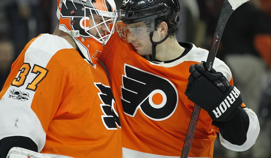 Philadelphia Flyers' Brian Elliott, left and Shayne Gostisbehere celebrate at the end of the third period of an NHL hockey game against the Toronto Maple Leafs, Tuesday, Dec. 12, 2017, in Philadelphia. The Flyers won 4-2. (AP Photo/Tom Mihalek)