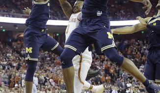 Texas guard Jacob Young (3) is blocked as he drives to the basket between Michigan defenders Charles Matthews (1) and Muhammad-Ali Abdur-Rahkman (12) during the second half of an NCAA college basketball game, Tuesday, Dec. 12, 2017, in Austin, Texas. Michigan won 59-52. (AP Photo/Eric Gay)