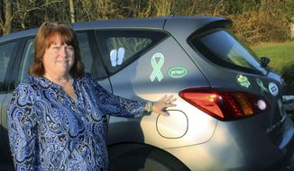 In this Nov. 30, 2017 photo, Suzanne Davenport poses beside her car on which she displays numerous stickers and magnets in memory of the 26 people killed in the December 2012 shooting at the Sandy Hook Elementary School in Newtown, Conn. Davenport said she's reluctant to tell strangers where she is from because of questions and conversations that invariably follow that revelation. (AP Photo/Pat Eaton-Robb)
