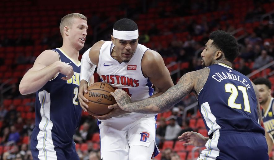 Detroit Pistons forward Tobias Harris, center, drives between Denver Nuggets center Mason Plumlee, left, and forward Wilson Chandler, right,  during the first half of an NBA basketball game, Tuesday, Dec. 12, 2017, in Detroit. (AP Photo/Carlos Osorio)