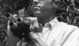 """In this undated photo provided by Bruce Brown Films, filmmaker Bruce Brown holds a camera while making one of his many surfing movies. Brown, whose 1966 surfing documentary """"The Endless Summer"""" molded the image of the surfer as a seeker and transformed the sport, died of natural causes at his home in Santa Barbara, Calif., Sunday, Dec. 10, 2017. He was 80. (Bob Bagley/Bruce Brown Films via AP)"""