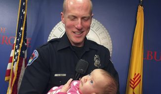 Albuquerque officer Ryan Holets holds his newly adopted daughter, Hope, after being recognized by the city of Albuquerque on Monday, Dec. 11, 2017. In September, Holets convinced a pregnant woman he found using heroin to let him adopt her unborn child. That baby, Hope, is now recovering for being born with an addiction. Holets and his wife have four other children. (AP Photo/Russell Contreras) ** FILE **