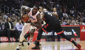 Los Angeles Clippers' Montrezl Harrell, left, is defended by Toronto Raptors' Serge Ibaka during the first half of an NBA basketball game Monday, Dec. 11, 2017, in Los Angeles. (AP Photo/Jae C. Hong)
