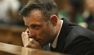 In this June 15, 2016, file photo Oscar Pistorius speaks on a mobile phone in the High Court in Pretoria, South Africa, during his sentencing hearing for murdering girlfriend Reeva Steenkamp. A South African prison spokesman says Pistorius, was bruised in an altercation with another inmate over telephone use. (AP Photo/Alon Skuy, Pool via AP, File)