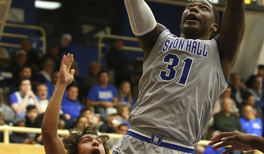 Seton Hall's Angel Delgado, right, attempts a shot as St. Peter's Elijah Gonzales, left,  defends during the first half of an NCAA college basketball game in South Orange, N.J., Tuesday, Dec. 12, 2017. (AP Photo/Rich Schultz)