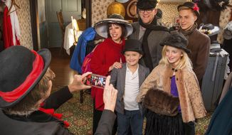 "This Nov. 14, 2015 image provided by the Cambridge/Guernsey County Visitors & Convention Bureau shows a family dressed up in Victorian-style clothing for a photo at the Imagination Station located in the Dickens Welcome Center in Cambridge, Ohio. The dress-up photo op is part of the annual Dickens Victorian Village in Cambridge which features scenes and characters inspired by the Victorian era and ""A Christmas Carol."" (Rick Lee/Cambridge/Guernsey County VCB via AP)"