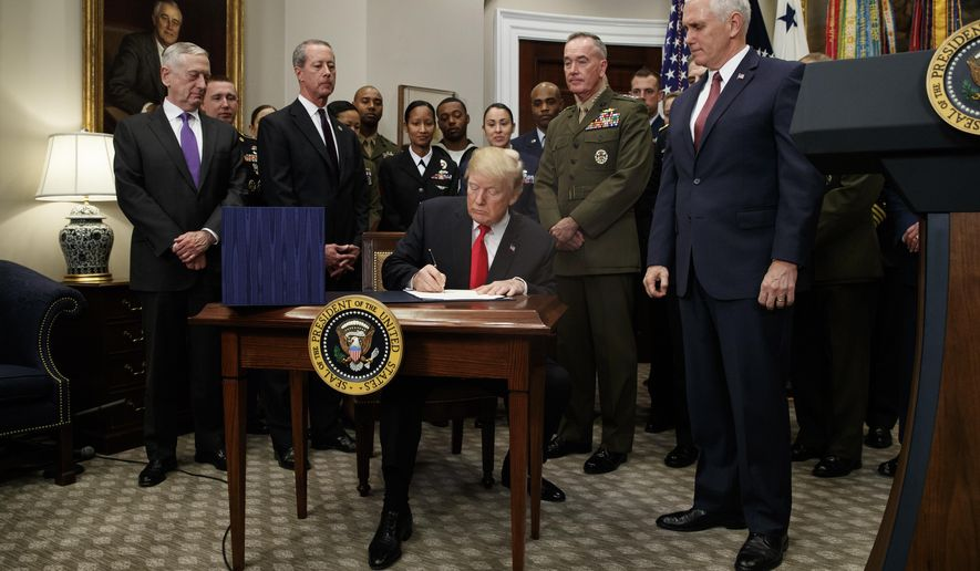 President Donald Trump signs the National Defense Authorization Act for Fiscal Year 2018, in the Roosevelt Room of the White House, Tuesday, Dec. 12, 2017, in Washington. (AP Photo/Evan Vucci)