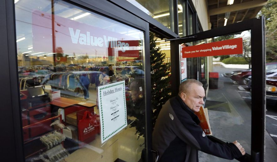 A shopper exits a Value Village store Tuesday, Dec. 12, 2017, in Edmonds, Wash. The company that operates 300 Value Village, Savers and other thrift stores in the U.S., Canada and Australia is suing Washington state Attorney General Bob Ferguson, saying his office has violated its rights by demanding $3.2 million to settle a three-year investigation. (AP Photo/Elaine Thompson)