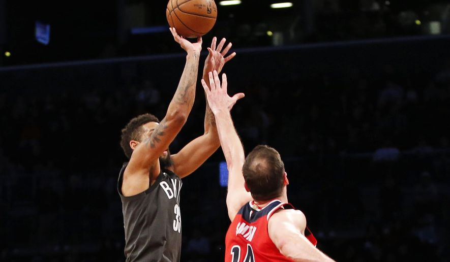 Brooklyn Nets guard Allen Crabbe, left, gets over the defense of Washington Wizards forward Jason Smith (14) as he shoots the winning three-point shot during the fourth quarter of an NBA basketball game, Tuesday, Dec. 12, 2017, in New York. The Nets defeated the Wizards 103-98. (AP Photo/Kathy Willens)