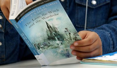 "Theint Wynn, 9, from John Quincy Adams Elementary School, browses  C.S. Lewis'  ""The Chronicle of Narnia: the Lion, the Witch and the Wardrobe"" after Walden Media presented a sneak preview of the new film ""Narnia"" , based on the book to students from Walker Jones Elementary and John Quincy Adams Elementary School at the Martin Luther King Library in northwest Washington. Tuesday November 1, 2005 ( Nancy Pastor / The Washington Times )"