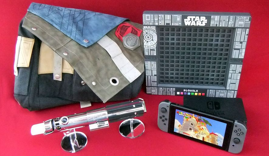 Gift ideas for gamers include the frontier bag from Activision's Destiny 2 Collectors Edition, a lightsaber from Lenovo's Star Wars: Jedi Challenges, Mattel's Star Wars Bloxels and Nintendo's Switch gaming system. (Photograph by Joseph Szadkowski / The Washington Times)