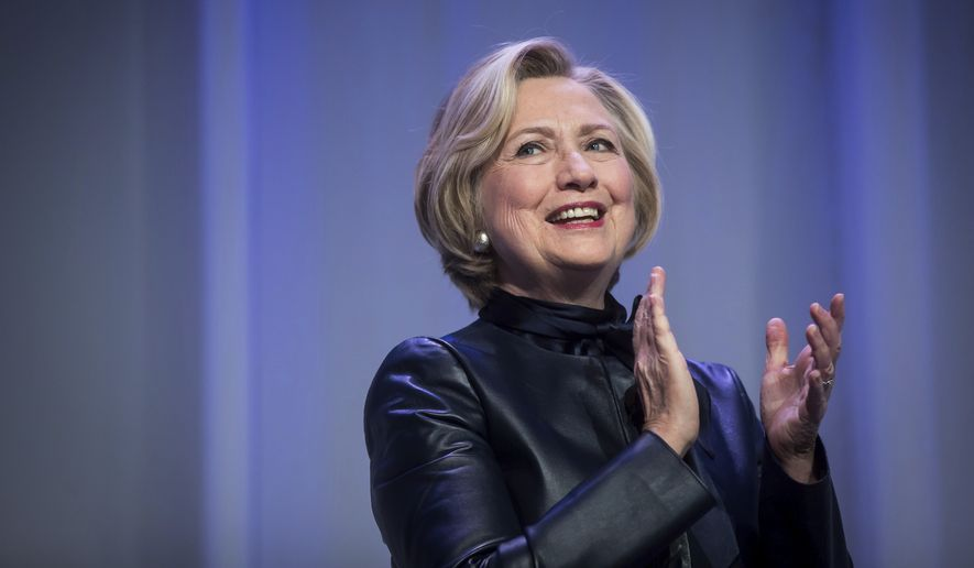Hillary Clinton applauds as she walks on stage for a book tour event in Vancouver, British Columbia, Wednesday, Dec. 13, 2017. (Darryl Dyck/The Canadian Press via AP)