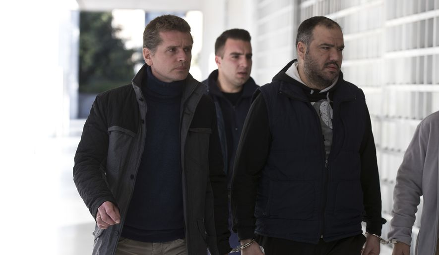 Russian cybercrime suspect Alexander Vinnik, left, arrives at Greece's supreme court in Athens, on Wednesday, Dec. 13, 2017. Greece's Supreme Court is due to rule whether to allow the extradition of a Russian cybercrime suspect to the United States to stand trial for allegedly laundering billions of dollars using the virtual currency bitcoin. (AP Photo/Petros Giannakouris)