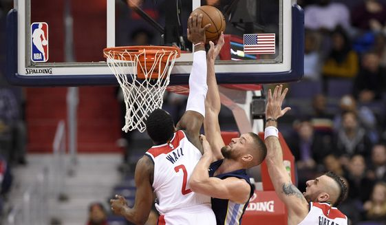 Washington Wizards guard John Wall (2) blocks Memphis Grizzlies forward Chandler Parsons, center, during the second half of an NBA basketball game, Wednesday, Dec. 13, 2017, in Washington. Also seen is Wizards center Marcin Gortat (13), of Poland. The Wizards won 93-87. (AP Photo/Nick Wass)