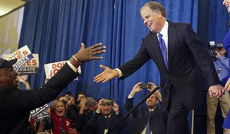 Doug Jones is greeted by a supporter before speaking during an election-night watch party Tuesday, Dec. 12, 2017, in Birmingham, Ala. Jones has defeated Republican Roy Moore, a one-time GOP pariah who was embraced by the Republican Party and the president even after facing allegations of sexual impropriety. (AP Photo/John Bazemore)