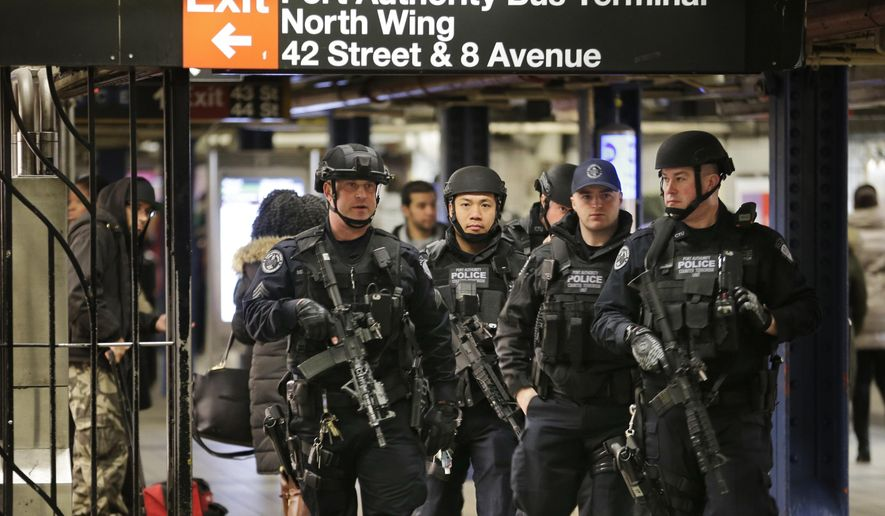 Police officers patrol in the passageway connecting New York City's Port Authority bus terminal and the Times Square subway station on Tuesday, Dec. 12, 2017, near the site of Monday's explosion. Commuters returning to New York City's subway system on Tuesday were met with heightened security a day after a would-be suicide bomber's rush-hour blast failed to cause the bloodshed he intended. (AP Photo/Seth Wenig)