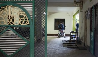 A man parks a motorcycle inside a building where 27-year-old Bangladeshi man Akayed Ullah, used to live in Dhaka, Bangladesh, Tuesday, Dec. 12, 2017. Bangladesh counterterrorism officers are questioning the wife and other relatives of Ullah, who is accused of carrying out a bomb attack in New York City's subway system, officials said Tuesday. (AP Photo/A.M. Ahad)
