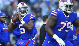 FILE - In this Sunday, Dec. 3, 2017 file photo, Buffalo Bills quarterback Tyrod Taylor (5) warms up prior to an NFL football game New England Patriots in Orchard Park, N.Y.  With his bruised left knee almost fully healed, Tyrod Taylor stood comfortably at the podium requiring no reminder of the doubts and adversity he's had to overcome in preparing to once again reclaim the Buffalo Bills' starting job. (AP Photo/Rich Barnes, File)