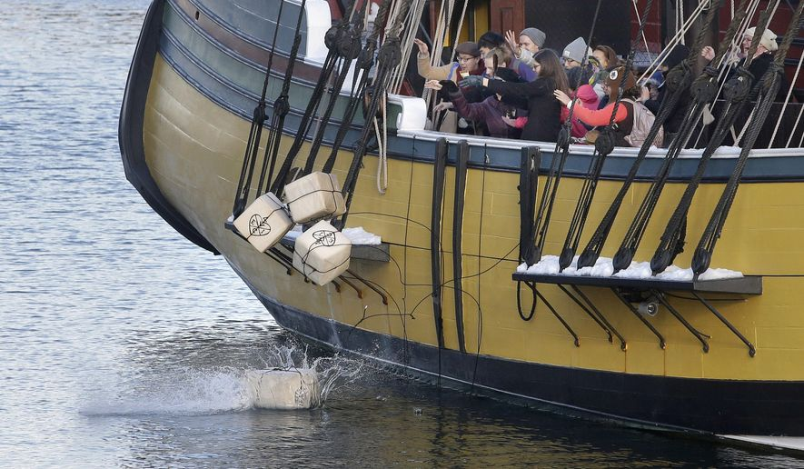 In this Monday, Dec. 11, 2017 photo, visitors to the Boston Tea Party Museum throw replicas of historic tea containers into Boston Harbor from aboard a replica of the vessel Beaver, in Boston. The museum is encouraging Americans to send unused tea leaves to toss into Boston Harbor as part of the Saturday, Dec. 16, 2017, annual re-enactment of the historic act of defiance that led to the Revolutionary War. (AP Photo/Steven Senne)