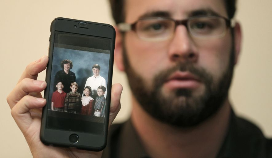 Jamey Anderson holds a photo on his phone of himself, bottom left, at the Word of Faith Christian School with classmates, from left, Liam, Risa Burgeson Pires, and Christopher Davies, and teachers Lisa Brown, top left, and Marty Roper, top right, during an interview in Charlotte, N.C., Monday, Dec. 11, 2017. Throughout his adolescence, Anderson says he was singled out as a rebel and suffered some of the most brutal treatment in the church. Among his transgressions: making a funny face at a classmate.  (AP Photo/Chuck Burton)