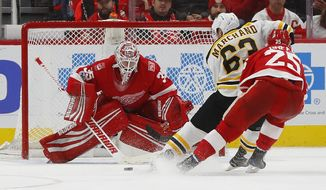Boston Bruins left wing Brad Marchand (63) scores against Detroit Red Wings goalie Jimmy Howard (35) during overtime of an NHL hockey game Wednesday, Dec. 13, 2017, in Detroit. Boston won 3-2. (AP Photo/Paul Sancya)