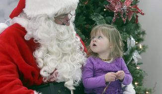 FILE - In this Saturday, Dec. 2, 2017, file photo, John Christensen talks with Zoey Martin, 2, while appearing as Santa Claus in Casper, Wyo. Christensen has portrayed Santa throughout Casper for more than two decades. (Elysia Conner/The Casper Star-Tribune via AP)