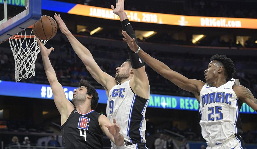 Los Angeles Clippers guard Milos Teodosic (4) has his shot blocked by Orlando Magic center Nikola Vucevic (9) as forward Wesley Iwundu (25) helps defend during the first half of an NBA basketball game Wednesday, Dec. 13, 2017, in Orlando, Fla. (AP Photo/Phelan M. Ebenhack)