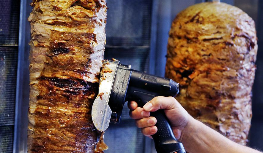 FILE -  In this Thursday, Nov. 30, 2017 file photo, a man slices cuts of meat from a rotisserie Doner spit inside a Doner restaurant cafe in Frankfurt, Germany.  The European Parliament narrowly defeated plans to ban an additive that is considered key in industrial meats for the popular doner kebab. Needing an absolute majority of at least 376 votes for a ban on phosphates, the legislature fell 3 votes short on Wednesday, Dec. 13, 2017.  (AP Photo/Michael Probst, File)