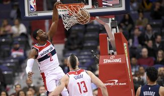 Washington Wizards guard John Wall (2) dunks during the first half of an NBA basketball game against the Memphis Grizzlies, Wednesday, Dec. 13, 2017, in Washington. Also seen is Wizards center Marcin Gortat (13) and Grizzlies forward Dillon Brooks (24). (AP Photo/Nick Wass)