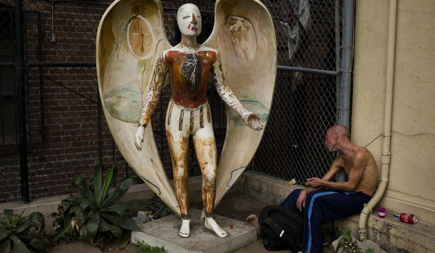 """Homeless drug addict Andrew Hudson, 33, reacts as he injects himself with heroin next to an angel statue Wednesday, Nov. 8, 2017, in the Skid Row area of downtown Los Angeles. """"It's miserable quitting, or trying - trying anything,"""" said Hudson. Skid Row is home to thousands of chronically homeless people on the edge of the downtown. No one shares the same story how they ended up in the center of poverty and despair. The streets are ruled by drugs day and night. Help exists, but too many turn to drugs to cope with their problems. (AP Photo/Jae C. Hong)"""
